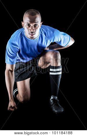Portrait of confident sportsman kneeling against black background