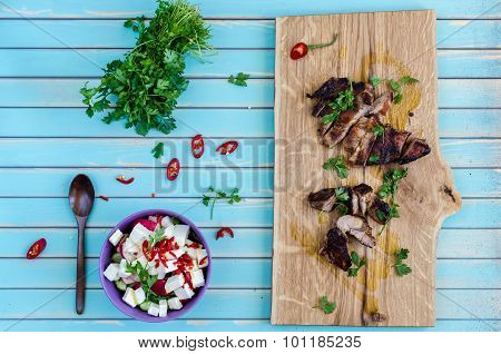 Grilled Pork Steak Cutting On Chopping Board With Vegetables Over Wooden Turquoise Background