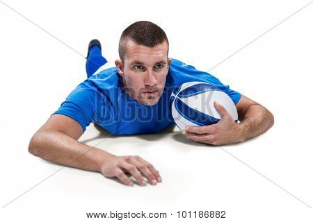 Rugby player looking away while lying in front with ball against white background
