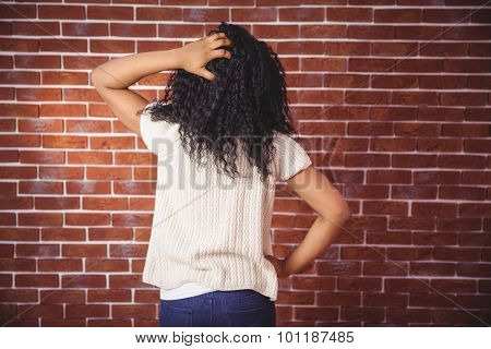 Young woman scratching her head on red brick background