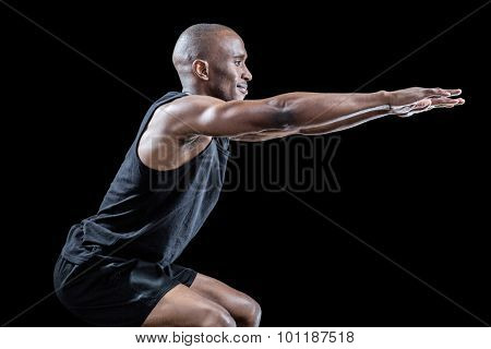 Side view of sportsman squatting against black background