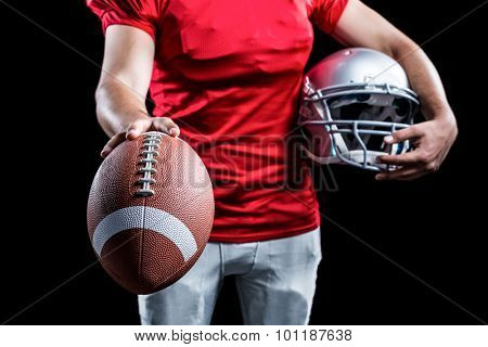 Mid section of sportsman showing American football while holding helmet against black background