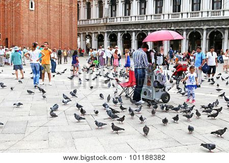 VENICE, ITALY - SEPTEMBER 2014 : People walking around at St Mark's Campanile (Campanile di San Marco) among a lot of pigeons and shops in Venice, Italy on September 15, 2014.
