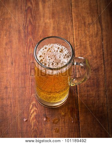 Mug of beer on wooden  background.