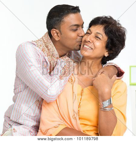 Portrait of happy Indian family at home. Indian 30s grown son kissing his mature 50s mother.