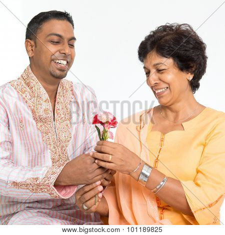 Portrait of happy Indian family celebrate mothers day at home. Mature 50s Indian mother received flower from 30s grown son.