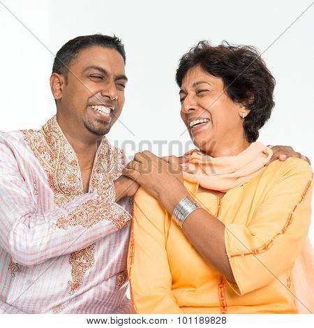 Portrait of happy Indian family having fun at home. Mature 50s Indian mother and 30s grown son laughing happily.