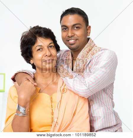Portrait of beautiful Indian family at home. Mature 50s Indian mother and her 30s grown son.