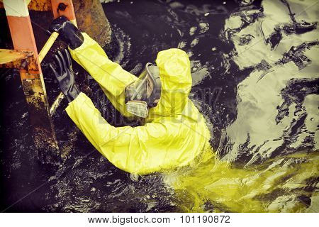 worker in protective suit in sea reaching ladder to save his life