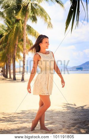 Slim Girl In White Frock Barefoot Poses Against Row Of Palms