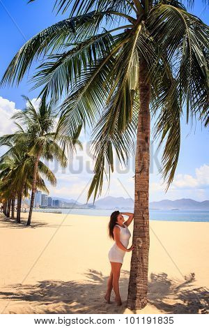 Girl With Big Bust In White Leans On Palm Against Row Of Palms