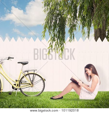 young woman reading a book in front of a white fence