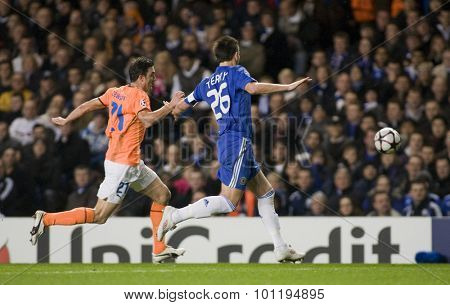 LONDON, ENGLAND. 08 December 2009. - Marcin Zewlakow playing for APOEL FC  and John Terry playing for Chelsea compete for the ball during the Uefa Champions League match,