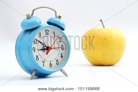 Picture of blue alarm clock and apple on a white background