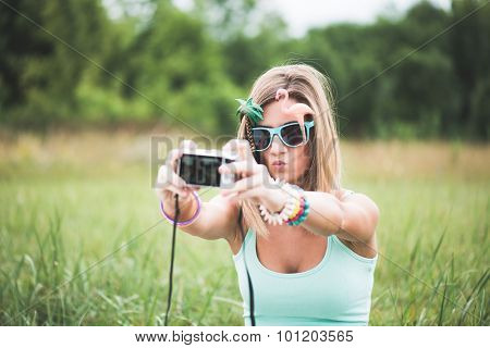 Young woman taking self portrait outdoor, wearing funny sunglasses and holding a compact camera