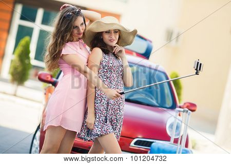 Two cute girlfriends taking selfies near the car