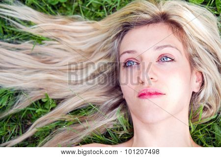 Young Girl With Long Blond Hair Lying On The Grass