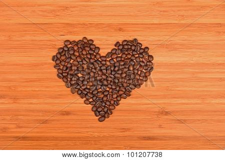 Heart Shaped Coffee Beans Over Bamboo Wood Background