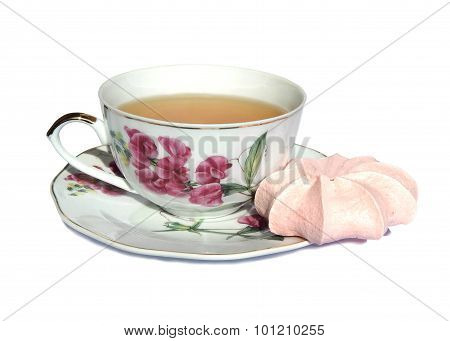 Pink meringue cake, white cup of green tea and saucer with a picture of pink flowers