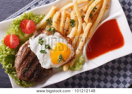 Grilled Steak, Fried Egg And French Fries Closeup. Horizontal Top View