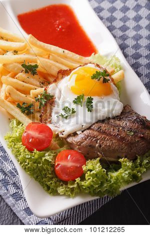 Delicious Beefsteak With Fried Egg And Fries On A Plate Close-up. Vertical