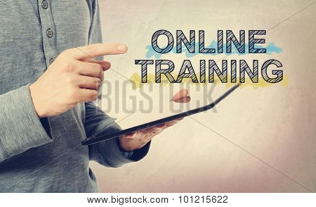 Young Man Pointing At Online Training Text Over Tablet Computer