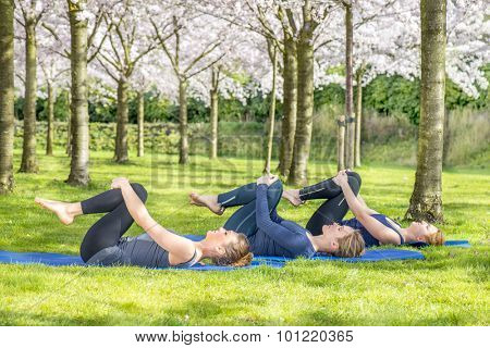 Young women practicing yoga in a blooming spring park