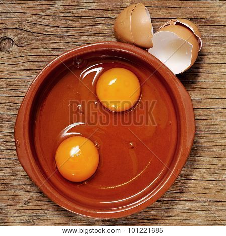 high-angle shot of an earthenware plate with some cracked chicken eggs on a rustic wooden table