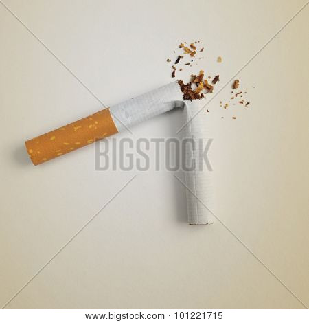 a broken cigarette on a beige background, symbolizing quitting smoking