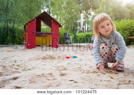 cute little girl in a sandbox on a playground
