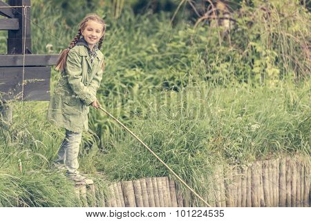 fisher girl with a rod on a river bank