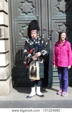 EDINBURGH UK - CIRCA AUGUST 2015: Scottish bagpiper dressed in a traditional tartan kilt with unidentified Asian tourist