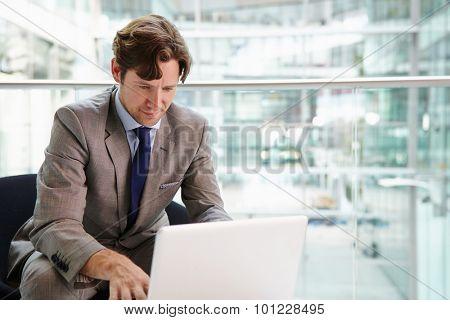 Corporate businessman using laptop computer, waist up