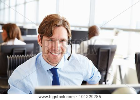 Man working in a call centre, looking to camera, close-up