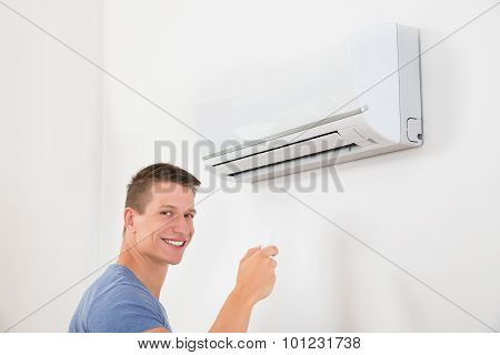 Man With Remote Control To Operate Air Conditioner