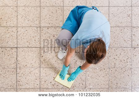 Janitor Rubbing Floor With Rag
