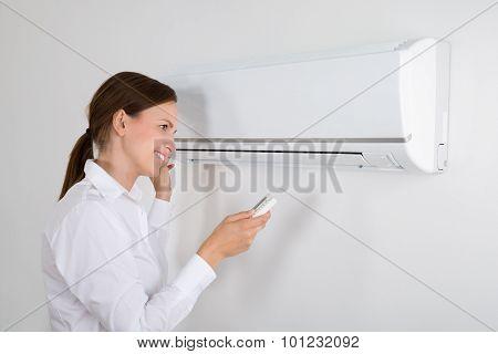 Businesswoman Operating Air Conditioner
