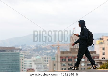 Man Wearing Hoodie Crosses Street In Contemporary San Francisco Scene