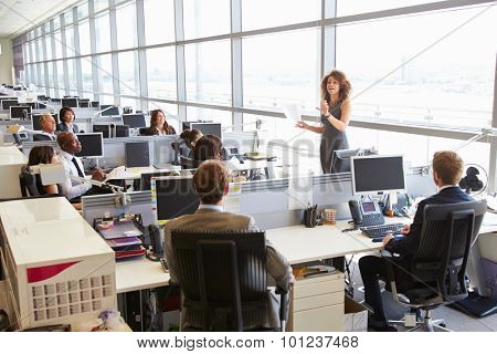 Female manager addressing workers in open plan office
