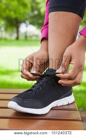 Woman tying her shoelace on running shoe in the park