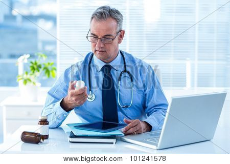 Male doctor looking prescription medicine bottle white sitting in hospital