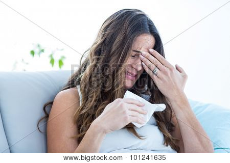 Sick woman crying on sofa at home