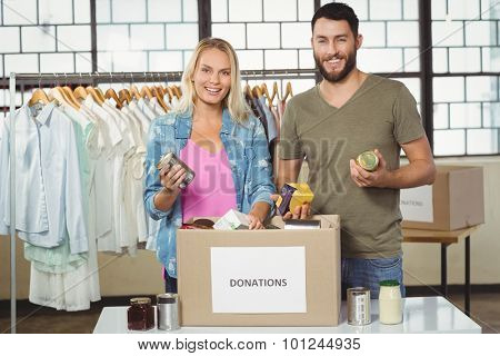 Portrait of happy colleagues smiling while holding products from donation box