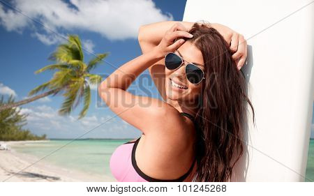 summer vacation, travel, surfing, water sport and people concept - young woman in swimsuit with surfboard on tropical beach