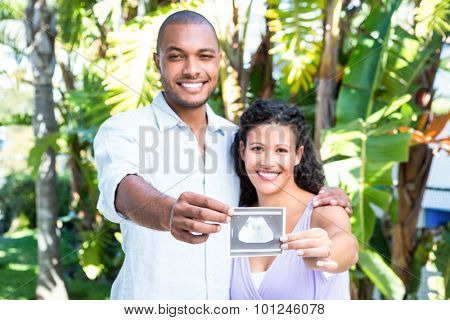 Portrait of happy husband with pregnant wife holding sonogram against white background