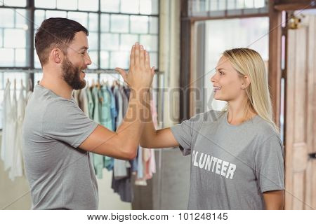 Smiling volunteer doing high five while working at office