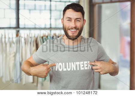 Man showing volunteer text on tshirt in office