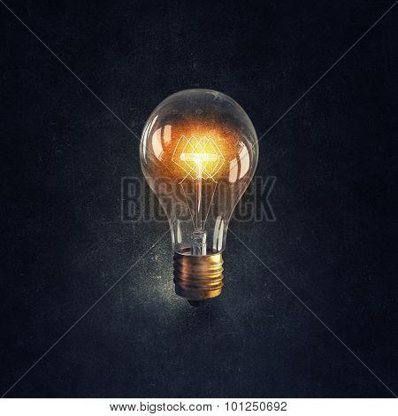 Glowing glass light bulb on dark bakground