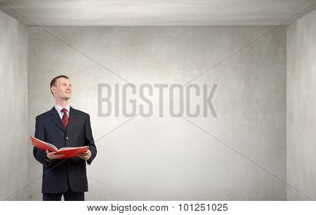 Young businessman with red book in hands