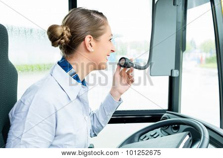 Bus driver woman speaking into the microphone making an announcement